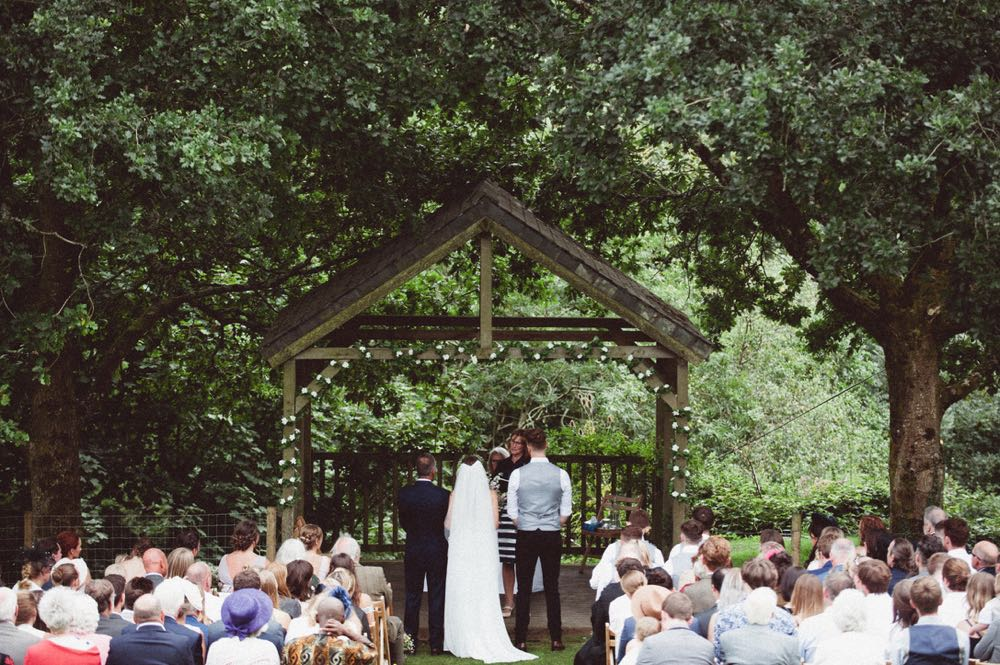 This is taken during an outdoor ceremony under the Oak Arbour. It is summer and the trees ae in ful leaf. The guests are seated in two colums of rows of chairs in front of the arbor with their abcks to the camera. The couple are under the arbour with thir back to the camera with the bride on the left and the groom on the right.  The image is taken from a distance with the Oak Arbour framing the shot.