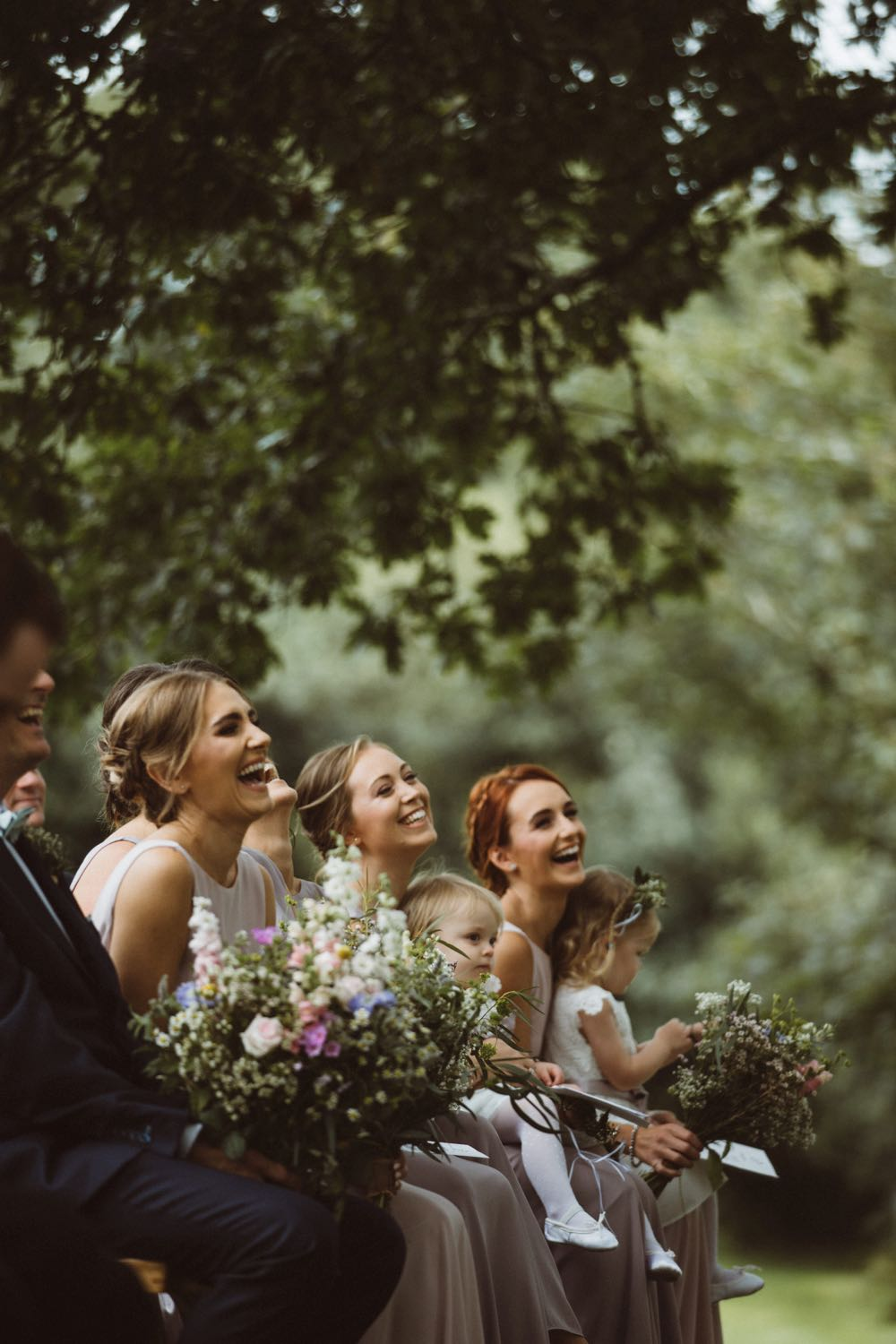 This is an image of 3 of the bridesmaids taken during the ceremony. They are shown from the shoulders up. They are surrounded by greenery. They are all smiling widely.