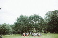This is taken during an outdoor ceremony under the Oak Arbour. It is summer and the trees ae in ful leaf. The guests are seated in two colums of rows of chairs in front of the arbor with their abcks to the camera. The couple are under the arbour. There are some straw bales set out behind the last row of chairs. The image is taken from a distance with the Oak trees shown in full.