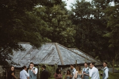 Some guests mingle in front of one of the cottages. You can seee the slate roof of the cottage in the background as the image is taken looking slightly down on the cottage. The guests are in the foreground and there are trees around the edges.