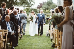 "The bride walks down the ""aisle\"" between the 2 colums of wooden chairs that are set out in front of the arbour. SHeis on her fathers arm. She is on the left walking towards the camera. She wears a full length white, sleeveless dress with lace details. She wears a veil. She has a bouquet of flowers, mostly green, in her right hand. The guests are stannding and turning around to see her."