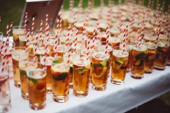 A shot of lots of glasses of Pimms waiting to get picked up by guests. The glasses are on a clothed white table. The glasses have Pimms and fruit in them and they have red, striped, paper straws.