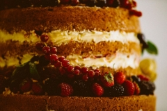 This i a close up shot of a naked spnge cake. You can see 4 layers and between the layers there is cream. There are lots of berries decorating the cake.