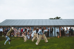A group of guests are having a sack race on the lawn in front of the Red Brick Barn