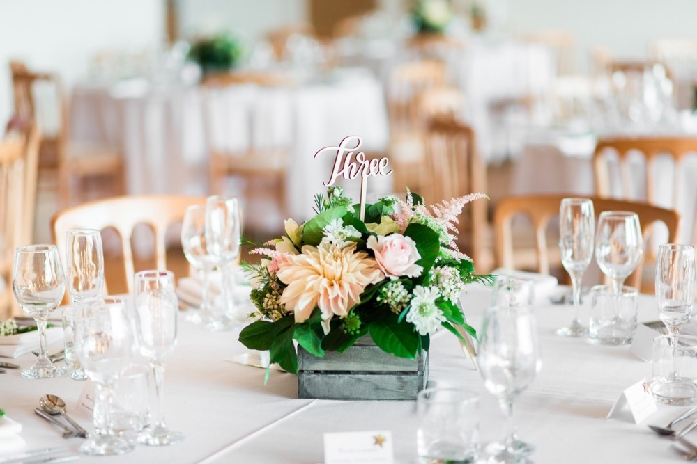 Table set up with round tables, white linen, cheltenham chairs and floral centre-pieces