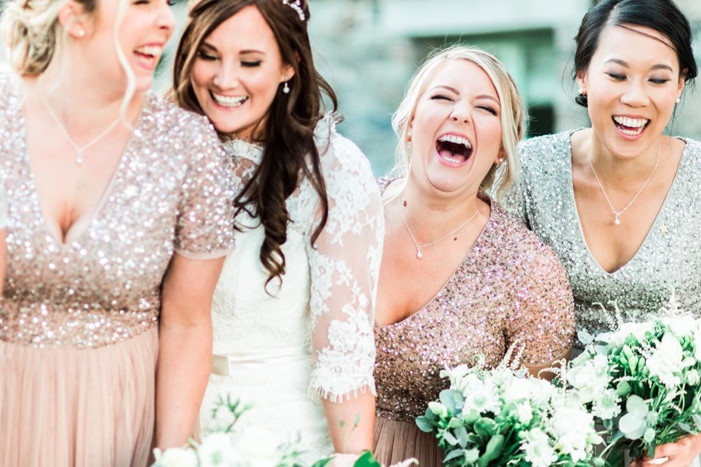 This is an image of the bride with 3 of her bridesmaids. It is a close up shot and they are laughing. There are 4 girlish the shot. The bride is second from the left. She wears a fitted white gown with lace details and 3/4 length lace sleeve.  She wears a delicate floral crown.  The bridesmaids are wearing  rose pink dresses with cap-sleeves and sequin embellishment.