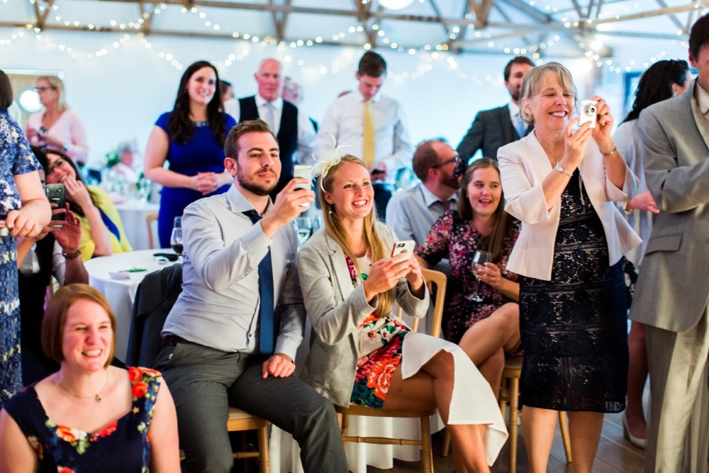 This picture is taken in the Red Brick Barn. It is of a group of wedding guests who are seated and standing in a group focussed on something that is out of shot. There are around 14 people in the group and they are taking pictures and smiling.