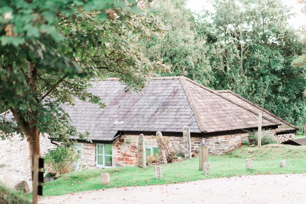 This is an image of cottage number 2. This detached cottage that sleeps 4 people. It is made of local cob that is gray and brown in colour. it has a grey slate roof. The cottage is surrounded by greenery.