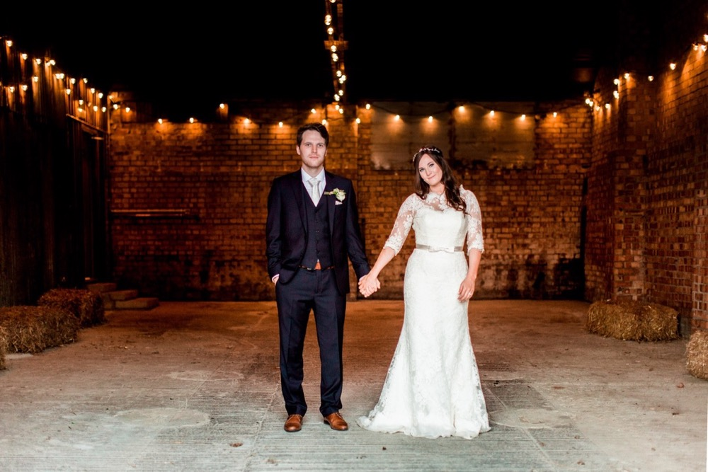 The bride and the groom are standing in the middle of the Really Rustic barn there is festoon lighting in the ceiling and much of the barn is in shadow. There are red brick walls and a rough concrete floor.  The bride and groom are standing in the middle of the shot and are standing side by side holding hands. The bride is on the right. She wears a fitted white gown with lace details and a delicate floral crown. The groom wears a dark suit with a white shirt and tie.