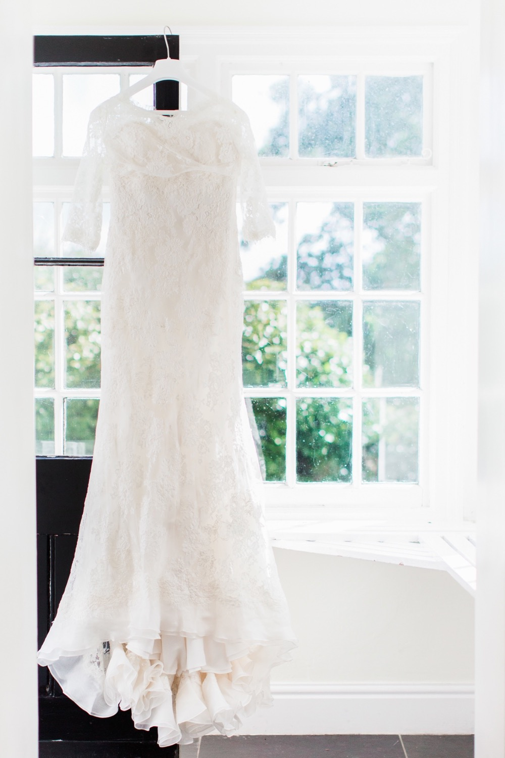 Lace, white wedding gown hanging in the porch of the the house. In the background there are Georgian say windows and a black painted front door that is open.