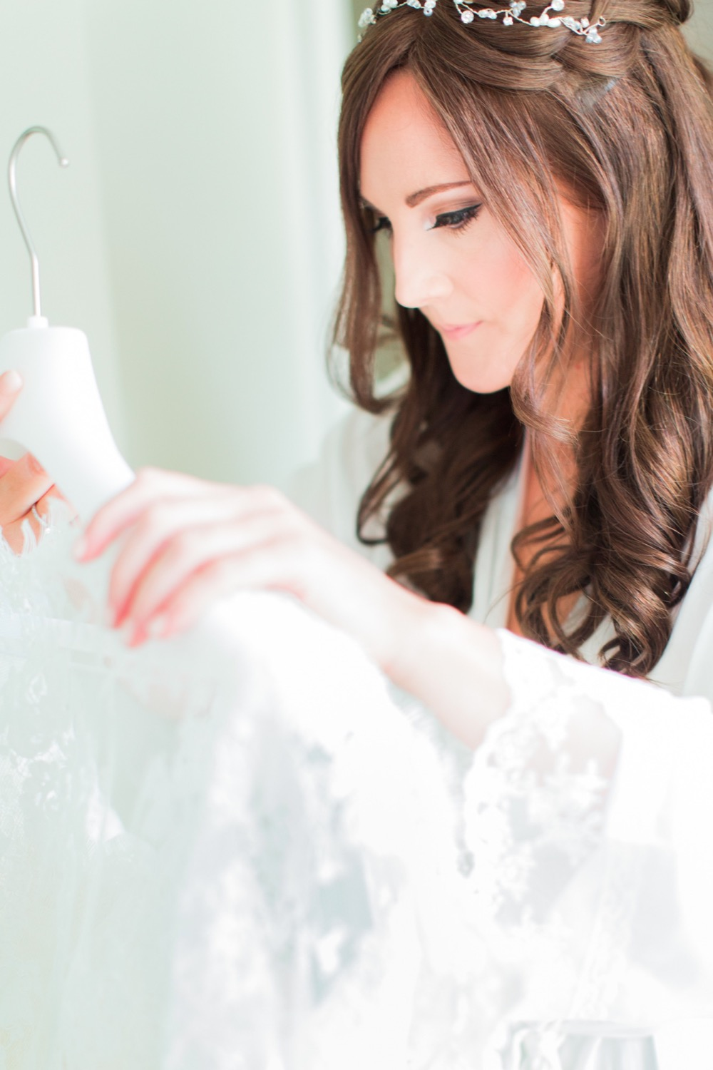 A close up shot of the bride holding her veil while getting ready. She has long dark hair that she wears loose.