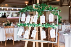 This picture is taken in the Red Brick Barn, It shows a detail shot of the couple's table plan, The table is made of a wooded picture frame that is draped in greenery. There are buff tags tied to the table plan and each is the name of a table with the guests names on it. In the background the Red Brick barn is set up with round tables with white linen and cheltenham chairs.