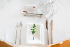Table set up with round tables, white linen and greenery for a place setting