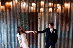 The bride and the groom are standing in the middle of the Really Rustic barn there is festoon lighting in the ceiling . The couple are shown only from the knees up. There is a corrugated iron wall behind them.  The bride and groom are standing in the middle of the shot and are standing side by side holding hands. The bride is on the left and is leaning away from he groom, She wears a fitted white gown with lace details and a delicate floral crown. The groom wears a dark suit with a white shirt and tie.