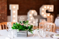 Table set up with round tables, white linen, cheltenham chairs and floral centre-pieces. Light up letters with L & S in the background.