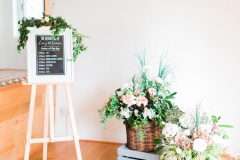 Decor details in the wedding barn, There is a white framed blackboard on an easel with an order of ceremony written on it. To the right of this there are some crates with florals in greenery, pink and white.