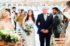 The bride and her father walk down the isle. The bride is on the left. She wears a fitted white gown with lace details and a veil. the pic is takes from the front of the wedding  barn and you can see bunting on the beams. The FOB wears a dark suit with a white shirt and a bow-tie. The bride holds a bouquet of white and pink flowers and it is hand-tied. There is a bridesmaid in the foreground to the left who holds a similar bouquet. The guests are standing bedside their chairs looking at the bride and FOG. Wooden folded chairs are set out in two columns of rows with an aisle down the middle.
