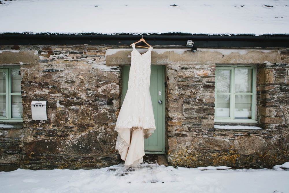 A white wedding dress hanging up outside above the front door of cottage number one. There is snowdon the ground