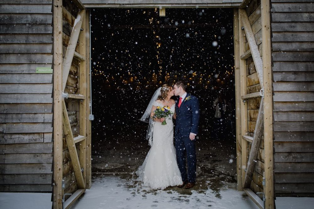A full length shot of the bride and groom standing at the entrance to the Really Rustic Barn. They are standing side by side and facing forwards but turning towards each other to kiss. The doors of the barn are open and they tower above the couple. You can see snow falling against the dark interior of the barn. The bride is wearing a white cap sleeved dress . She has dark hair that she is wearing loose with a veil. . The groom is wearing a dark grey suit.