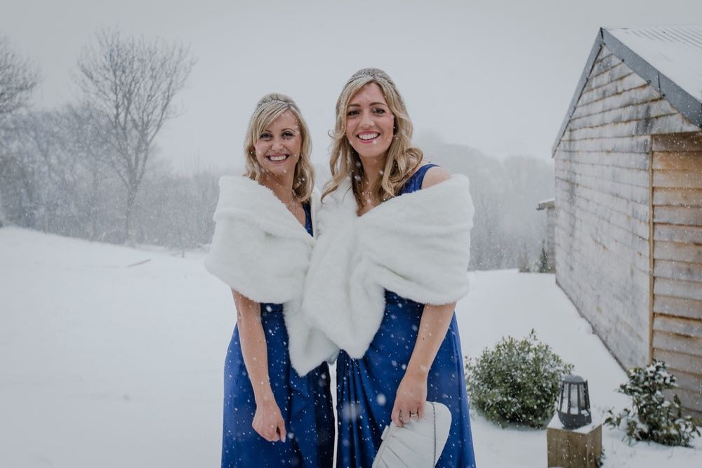 A picture of two bridesmaids standing outside in the snow. The shot is from the knees up. There is lots of snow in the background. The bridesmaids both have blonde hair that they are wearing loose. There are wearing blue dresses and white fur stoles