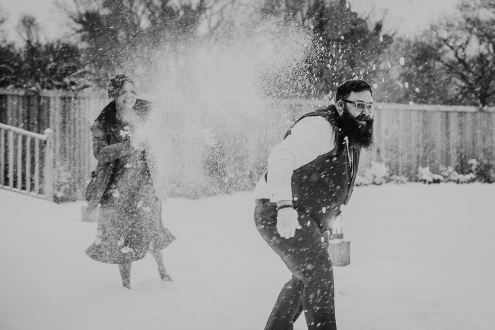 A back and white shot of two wedding guests having a snowball fight. The woman is wearing a cost and is covered in snow. The man is bearded and is in shirt sleeves.