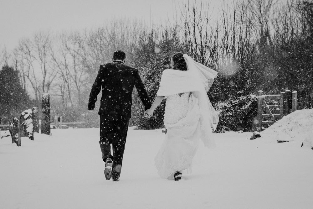 A full length shot of the bride and groom walking away from the camera outside in the snow. . They are walking side by side and facing forwards but turning towards each other. The bride is on the right. The bride is wearing a white cap sleeved dress . She has dark hair that she is wearing loose with a veil. . The groom is wearing a dark grey suit.