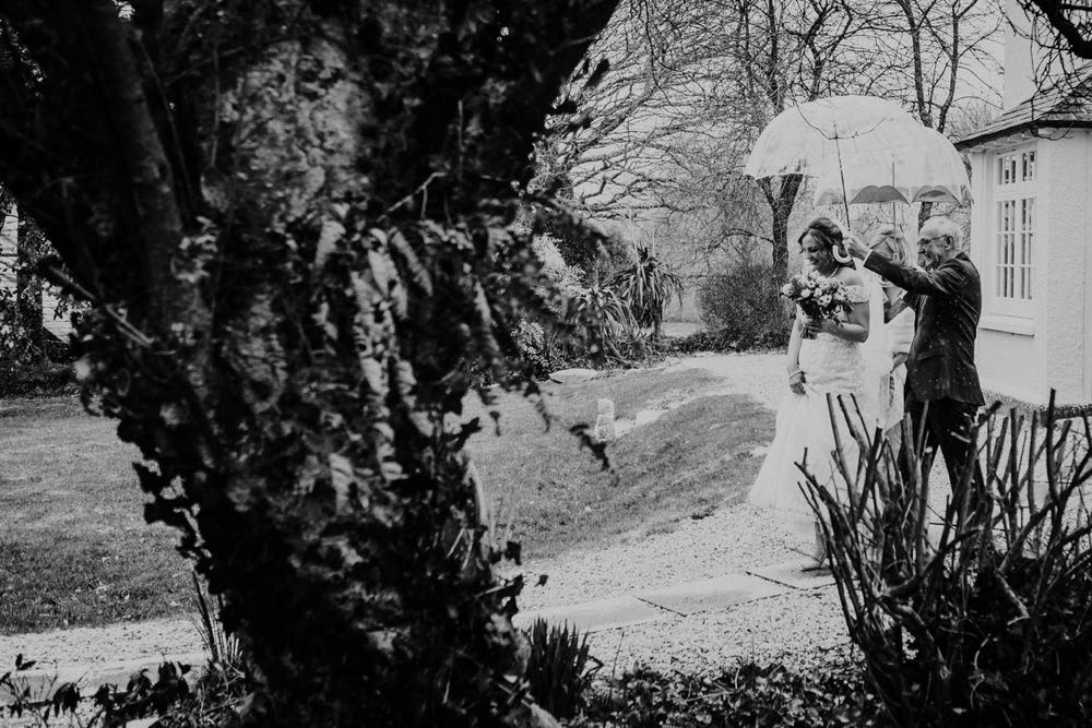 A black and white shot of a couple walking outside sheltering under an umbrella from the snow.