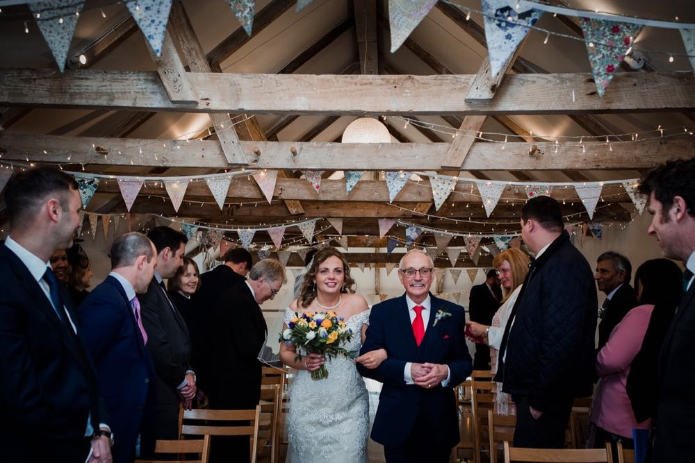 """A bride walking down the """"aisle"""" in the wedding barn  with her dad. The bride is on the left and they are linking arms. The bride is carrying a bouquet in her right hand. She is wearing a white cap sleeved dress . She has dark hair that she is wearing loose with a veil. You can see bunting and beams above their heads. The guests are standing and facing forward but turning their heads towards the bride and her father"""