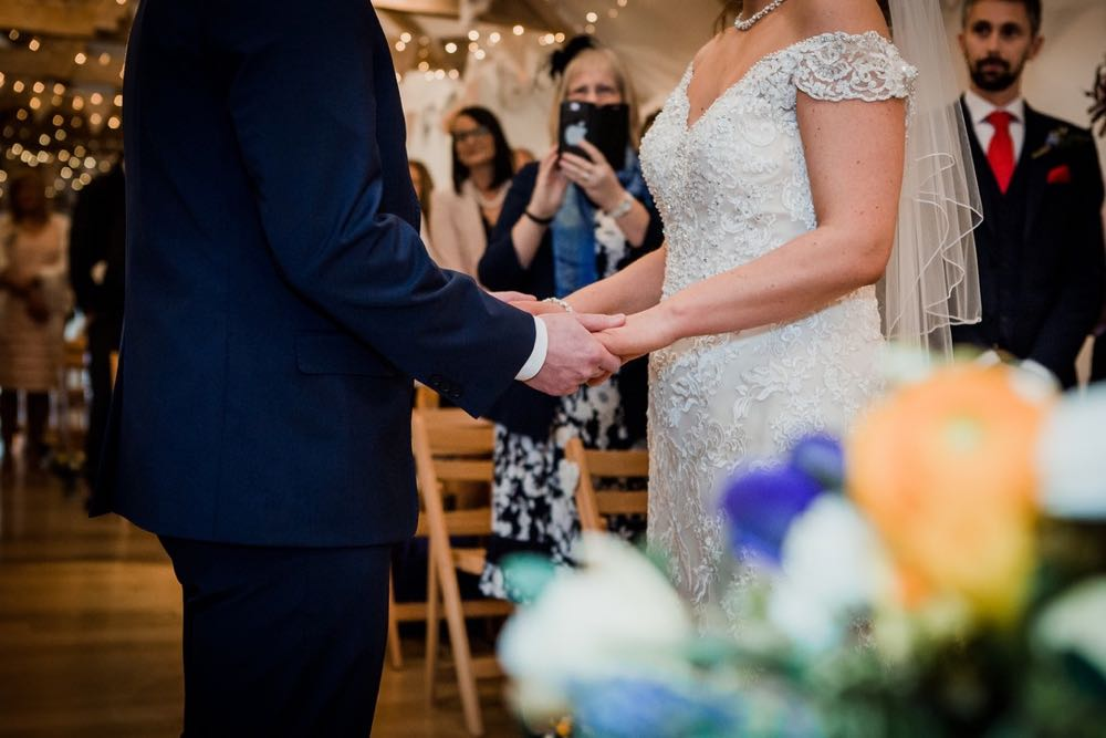 A close up shot of the bride and groom for the knees to their necks  in the wedding barn while they exchange vows. There are some flowers in the foreground