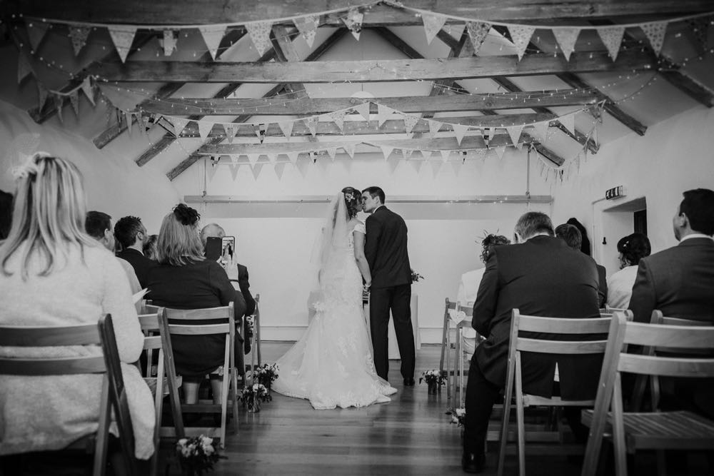 """A black and white shot of the couple embracing at the front of the wedding barn after they have exchanged their vows. You can see beams and bunting above their heads. Their guests are seated on wooden chairs on either side of the """"aisle"""""""
