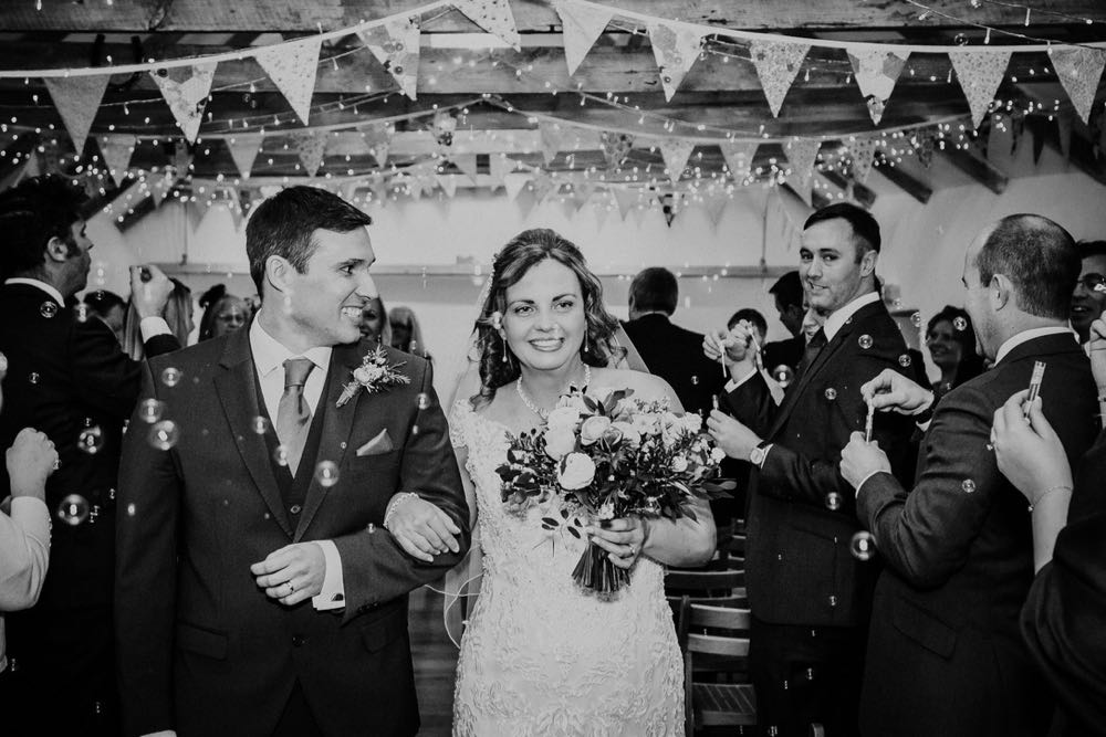 """A black and white shot of the couple leaving the wedding barn after the ceremony.  They are walking down the """"aisle"""" in the wedding barn  arm in arm. The bride is on the right. The bride is carrying a bouquet in her left hand. She is wearing a white cap sleeved dress . She has dark hair that she is wearing loose with a veil. You can see bunting and beams above their heads. The guests are standing and facing forward but turning their heads towards the bride and her groom."""