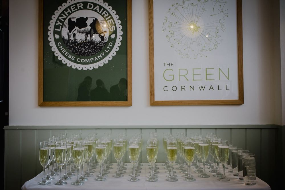 An image of charged glasses of champagne set up on a clothed white table. Above the table there are 2 framed pictures on the wall. One is a vintage advert for Yarg cheese and the other is the logo of The Green.