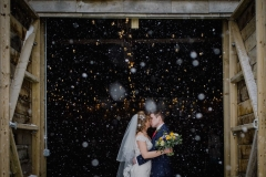 A waist up shot of the bride and groom standing at the entrance to the Really Rustic Barn. They are standing side by side and facing forwards but turning towards each other to kiss.The bide has her bouquet in her right hand. The doors of the barn are open and they tower above the couple. You can see snow falling against the dark interior of the barn. The bride is wearing a white cap sleeved dress . She has dark hair that she is wearing loose with a veil. . The groom is wearing a dark grey suit.