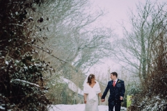 A shot from the knees up of the bride and groom walking away from the camera outside in the snow. . They are walking side by side and facing forwards but turning towards each other. The bride is on the left. The bare winter trees are towering above them. The bride is wearing a white cap sleeved dress . She has dark hair that she is wearing loose with a veil. . The groom is wearing a dark grey suit.