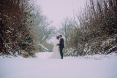 A  full length shot of the bride and groom standing embracing in the snow.. They are standing side by side and facing towards each other. The bride is on the left. The bare winter trees are towering above them. The bride is wearing a white cap sleeved dress . She has dark hair that she is wearing loose with a veil. . The groom is wearing a dark grey suit