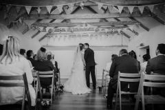 "A black and white shot of the couple embracing at the front of the wedding barn after they have exchanged their vows. You can see beams and bunting above their heads. Their guests are seated on wooden chairs on either side of the ""aisle"""