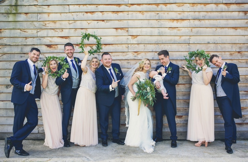 This image shows the bridal party including the bride and groom, 3 bridesmaids and 3 groomsmen. The group is standing on a lin (boy, girl, boy, girl etc. ) with the bride and groom 5th and 6th from the left. The  bridesmaids are holding greenery hoops which they have as an alternative to bouquets. This is a light hearted and informal shot with the bridesmaids looking through the hoops and waving them in the air. The groom and groomsmen wear navy suits, gray waistcoats, white shirts and blue ties. The bride wears  a full-length, sleeveless, white dress with lace details  and a beaded bodice. The bridesmaids wear pale pink dresses similar in style to the bride's.