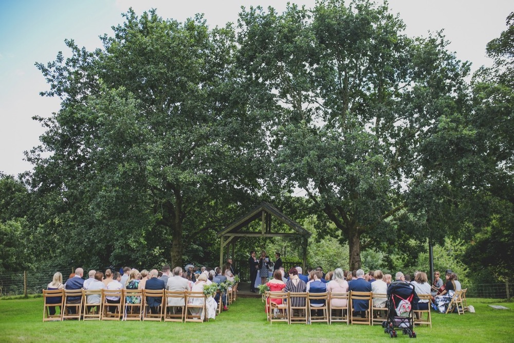 This is an image of the Oak Arbour just before the couple arrive. The arbour is a wooden structure with four corner posts supporting a pitched roof. The arbour has a large Oak Tree on each side. The trees are in full leaf. This photo is taken from a bit of a distance and the whole of the Oak Trees are in the frame. There is a clothed table (white) also under the arbour.  It is a summers day and the trees are in full leaf. You can see their guests sitting in front of the arbour in two columns of rows of seats.. The guests are looking at the couple towards the arbour and have their backs to the camera. You can see  a clothed table under the arbour.
