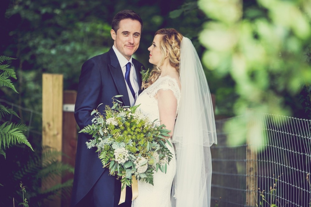This is an image of the bride and groom standing in the woods. They are standing side by side with the groom on the left. The bride is angled slightly inwards towards the groom. The bride has a bouquet of greenery in her left hand.  The groom is wearing a navy suit, gray waistcoat, white shirt and blue tie. The bride wears  a full-length, sleeveless, white dress with lace details  and a beaded bodice. There is greenery in the background and a leafy branch in the foreground. There is some sheep fencing behind the couple.