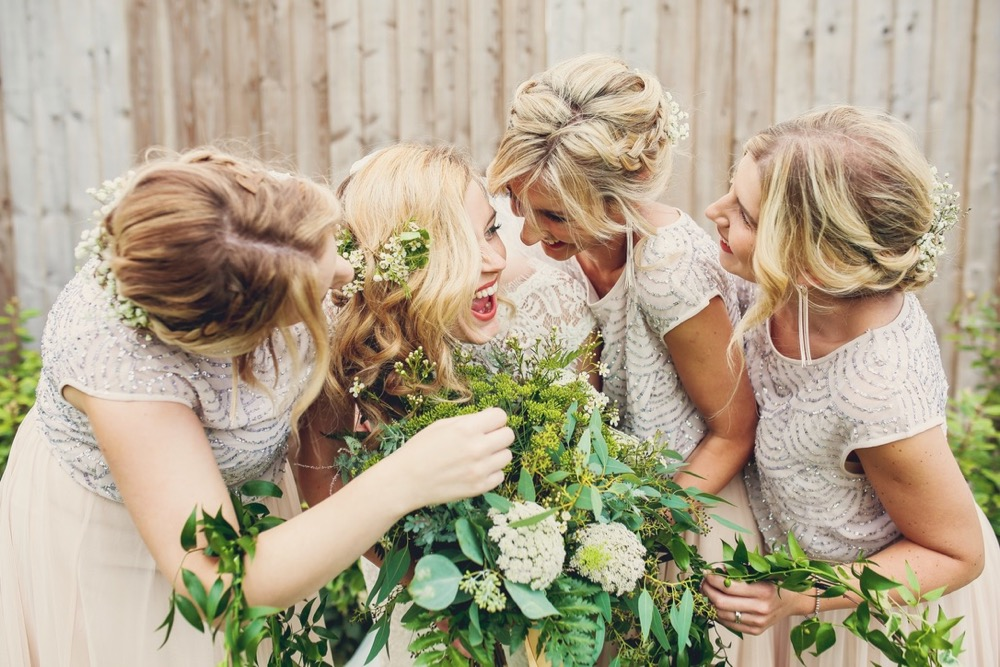 This image shows the bride and 3 bridesmaids The group is standing in a line in front of an oak fence. With the bride and groom 2nd from the left. The  bridesmaids are holding greenery hoops which they have as an alternative to bouquets. This is a light-hearted and informal shot with everyone laughing and bending in towards the bride. They are sharing a joke. All have blond hair.