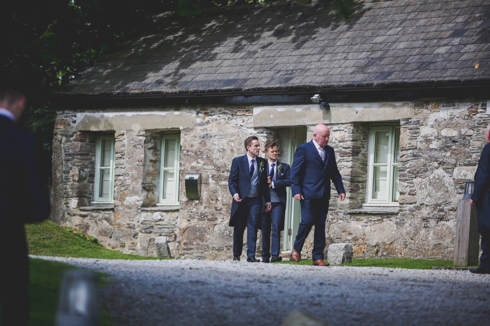 This is a photo the groom and his 3 groomsmen walking out of cottage number 1. The groom and groomsmen wear navy suits, gray waistcoats, white shirts and blue ties. Cottage number one sleeps two people. The property is single storey. The photo shows the full width of the cottage. In the background you can see trees which are in leaf. In the foreground you can see two patches of grass one on the left and one on the right and in the front there is gravel. The cottage is made of granite stone and is brown and grey in colour. The roof is constructed of grey slate and is pitched with the roof line running from left to right of the photograph along the length of the cottage. In the middle of the front of the cottage there is a wooden door that is painted pale green on either side of the story there are two windows on each side of this door. They are Georgian style sash windows and also painted green. On the right hand side of the cottage the gable end has hanging slate on it. There is a French window in this end of the cottage and it is also painted green. In the foreground of the picture there is a light bollard for outside lighting.