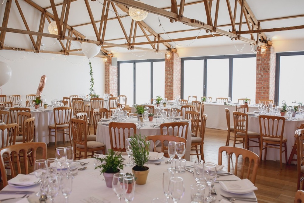 This is an image of the Red Brick barn set up for a wedding meal. The room has oak floors and white walls and ceiling. The tables are round and covered in white table cloths. There are bi-fold doors to the front of the room away from the camera. Light is streaming in the windows. There are wooden (cheltenham-style) chirs around the tables. Youc an see 5 tablesin the picture. The tables are laid up with white crockery and silverware. There are pots of green plants in the centreof each table as centre pieces. There are no people in the room yet.
