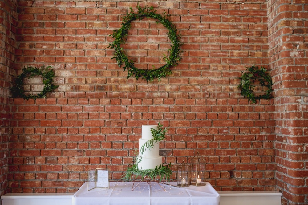 This is a picture of the cake table set up against the red brick wall in the Red Brick Barn. The shot shows quite a  lot of the wall and the cake is quite small in comaprison near the bottom of the image. The cake is simple, whie and 3 tiered , decorated with green leaves.  It is placed on a white-clothed table but only the table top. On the wall behind the cake