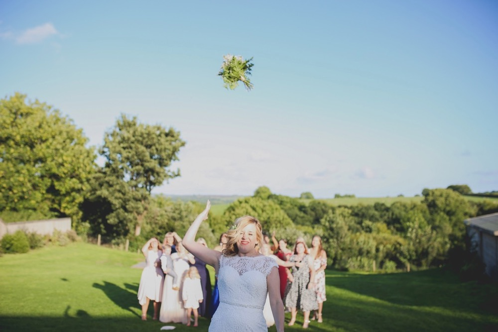 The bouquet toss. The bride is srtanding facing the camera with a group of female guests gathered behind her. The sky is bright blue and the shadows are long indicating that is it early evening. Everyone is standing on a green lawn and there are trees in the backgound in full leaf. The bride has her eyes squeezed shit and is throwing her bouquet over her right shoulder, as hard as she can, with her right arm. The bride wears  a sleeveless, white dress with lace details  and a beaded bodice.