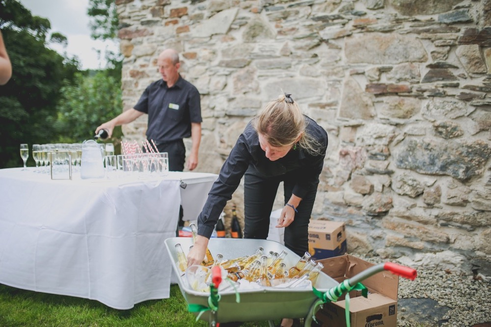 This picture shows 2 members of staff getting ready to serve drinks at an outside bar. They are setting up  in front a a stone wall that is made of gray and brown granite stones. There is a table clothed in a white table cover. One member of staff is settgin out glasses. Another is placing bottles of beer into a wheelbarrow that is full of ice. teh staff are both male and they are wearing black shirts and black trousers