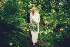 This is an image of the bride and groom walking in the woods. They are walking in single file on a narrow path with the groom behind. They are walking in a tunnel of greenery. The bride has a bouquet of greenery in her left hand.  The groom is wearing a navy suit, gray waistcoat, white shirt and blue tie. The bride wears  a full-length, sleeveless, white dress with lace details  and a beaded bodice.