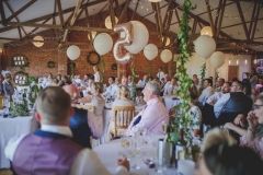 This is an image of the Red Brick barn during a wedding meal. The room has oak floors and a red brick wall and white ceiling. The tables are round and covered in white table cloths. There are wooden (cheltenham-style) chirs around the tables. You can see around 5 tables in the picture. The tables are laid up with white crockery and silverware. There are pots of green plants in the centreof each table as centre pieces. There are people seated at the tables. There are balloons rising up towards the A-frame beamsin the pitched roof.