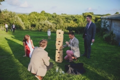 A group of guests are playing Giant Jenga on a green lawn, The shadows are long in this shot indicating that it is early evening. There are a group of 4 guests playing the game. In the background there are many green trees.
