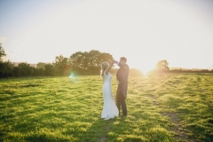 This is an image of the bride and groom standing in a field at sunset. . They are standing in the middle of the picture. The sun is setting behind them and there is a row of green treesin the background.  The groom is wearing a navy suit, gray waistcoat, white shirt and blue tie. The bride wears  a full-length, sleeveless, white dress with lace details  and a beaded bodice.