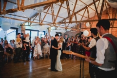 This is an image of the Red Brick barn during a wedding reception. The room has oak floors and a red brick wall and white ceiling. There are people grouped in the far right hand corner of the room in front of a set of bi-fold doors watching the bride and groom having their first dance. In the foreground is a musician playing a guitar with his back to the camera.  There are balloons rising up towards the A-frame beams in the pitched roof.  The room has oak floors and white walls and ceiling. The tables are round and covered in white table cloths. There are bi-fold doors to the front of the room away from the camera. Light is streaming in the windows. The lights are dimmed and the couple are dancing closely in the middle of the floor.